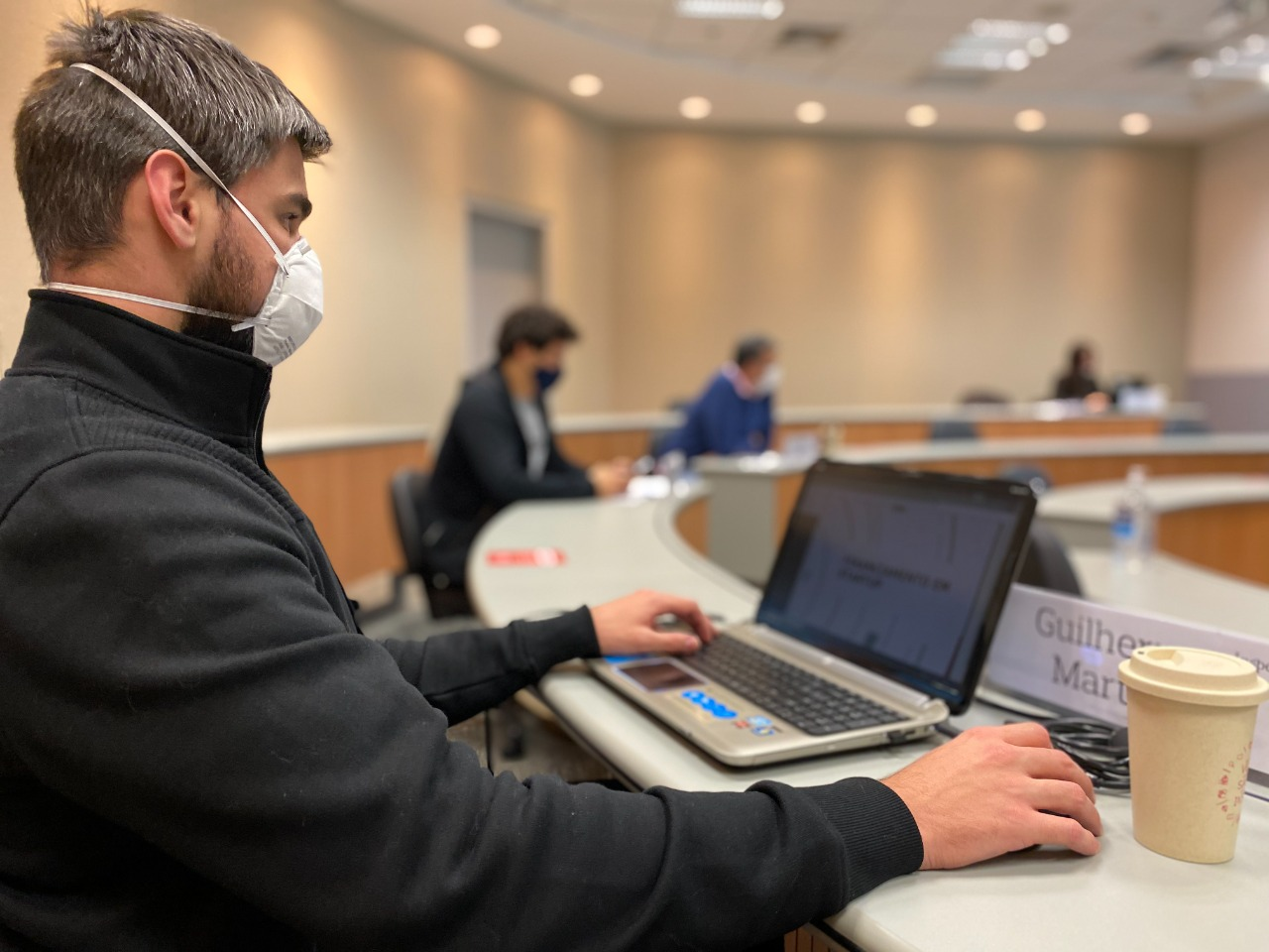 student from the executive education classes, he wears a mask and use his computer